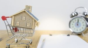 Alarm clock, house model and shopping cart model, home buying moment concept