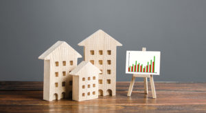 Residential buildings and easel with a positive growth trend chart. Market growth, attracting investment. Raising taxes and house maintenance. Real estate price increases. High demand and value
