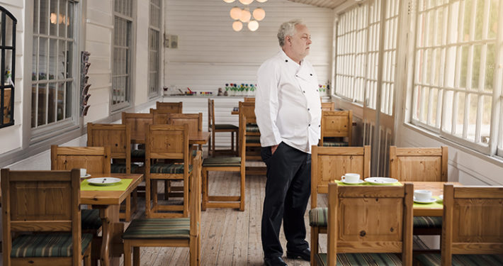 Restaurant owner standing in his empty restaurant.