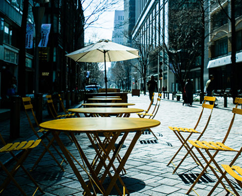 Empty Chairs And Tables At Cafe In City