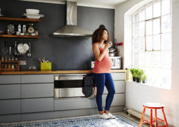 A pregnant lady looks out of her kitchen window
