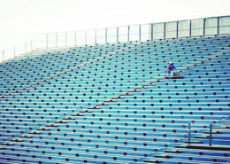 Man Sitting On Bleachers At Stadium