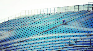 Man Sitting On Bleachers At Stadium