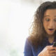Close up of mixed race woman gasping at cell phone