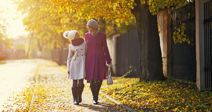 Mother and daughter walking in the street in the autumn
